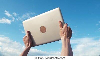 Male hands raise laptop up. Blue sky on background. Success, achievement gesture