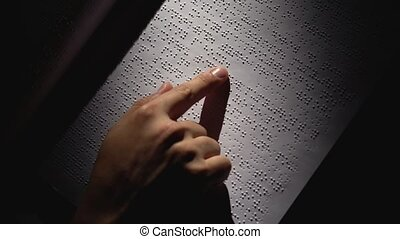 Male Hands Reading a Braille Book in dark room . Close up -...