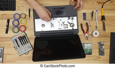Male hands repairing computer details and using laptop on wooden table, top view
