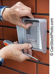 Male hands repairing intercom