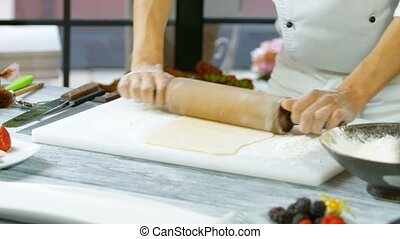 Male hands rolling out dough.