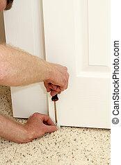Male Hands Screwing in a Door Guide