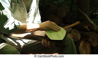 Male hands sharpening dirty old rusty axe with a grindpaper...