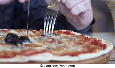 Male hands slicing pizza with ham, olives, cheeze and mushrooms. 3840x2160