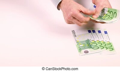 Male hands spread out the money in denominations of 100...
