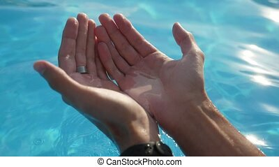 Male hands taking blue water in handfuls and raising it in ...