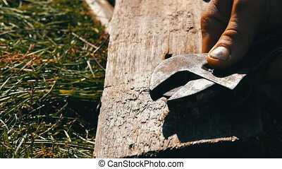 Male hands tighten wrench and screw on a wooden board close...