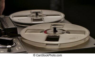 Male hands turn on and off a vintage professional analog reel to reel tape recorder. Transparent rotating coils reproduce old music. Retro tape. Close up. Slow motion