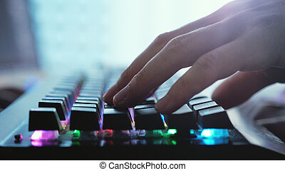 Male hands typing on a laptop keyboard by the panoramic window