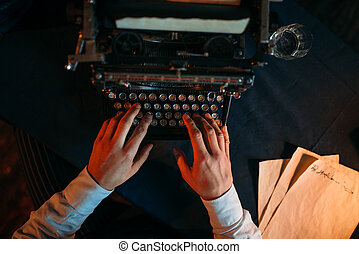 Male hands typing on retro typewriter, top view. Dark blue...