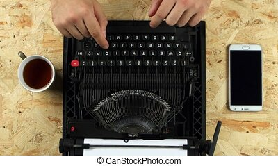 Male hands typing on the typewriter. View from above - Men's...