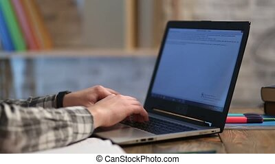 Male hands typing text on modern laptop keyboard