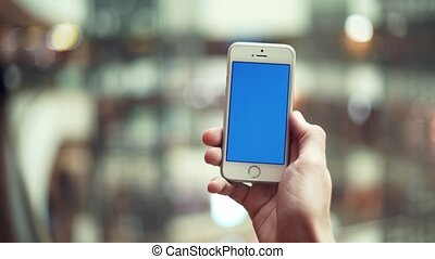 Male hands using smartphone with blue display in shopping mall