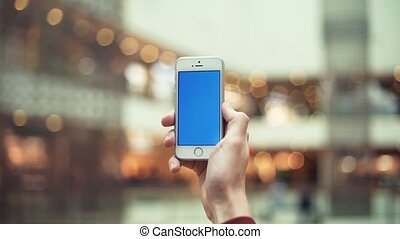Male hands using smartphone with chroma screen in shopping center