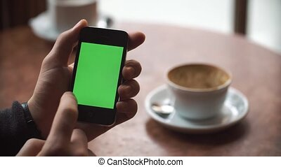 Male hands using smartphone with green screen in Cafe.