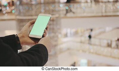 Male hands using smartphone with green screen in shopping mall. Holiday decorations at background