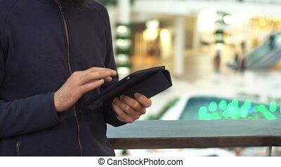 Male hands using tablet in shopping mall