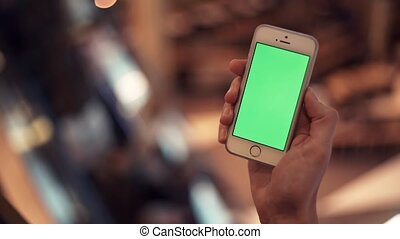Male hands using telephone with green display in shopping mall