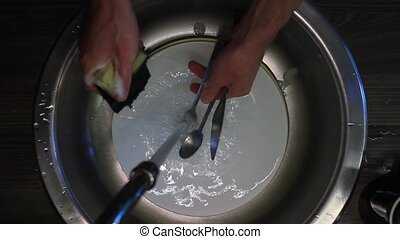 Male hands wash kitchenware in a wash basin HD