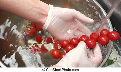 Male hands washing cherry tomatoes.