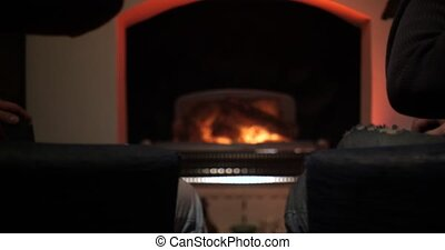Male hands with drinks in glasses on fireplace background. Friends cheers with copgnac in glasses sitting by fire. Hands clinking cognac glasses near the fireplace.