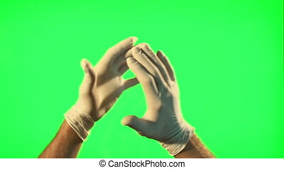 Male hands with surgical gloves clapping on green screen