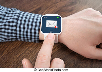 male hands with white smartwatch with email on the screen over a wooden table in an office