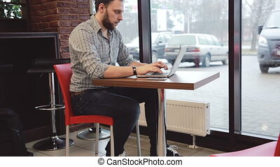Male hands working on laptop in cafe