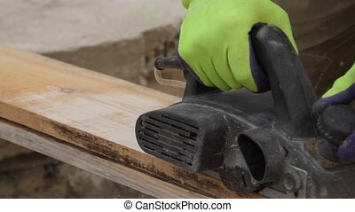 Male hands working with wooden plank electric planer Slow motion Chips and sawdust fly apart