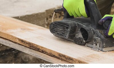 Male hands working with wooden plank electric planer Slow motion