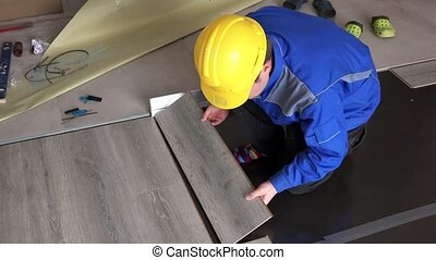 Male handyman lay wooden laminate boards on floor in new...