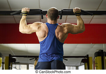 Male heavyweight athlete doing pull-ups, perfect masculine body, healthy life