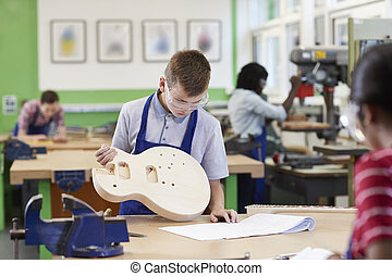 Male High School Student Building Guitar In Woodwork Lesson