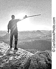 Male hiker athlete on a rock during a trail in the mountains, far view of the region.