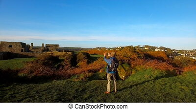 Male hiker hiking in countryside 4k - Rear view of male...