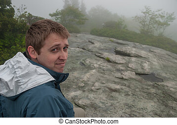 Male Hiker in Fog on Rock