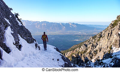 hiker on a hiking trail in early winter in the mountains