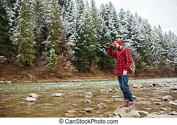 Male hiker standing on the stone in river