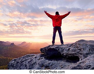 Male hiker walking on top of mountain looking at beauty morning landscape.