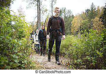 Male Hiker With Friends Walking On Forest Trail - Full...