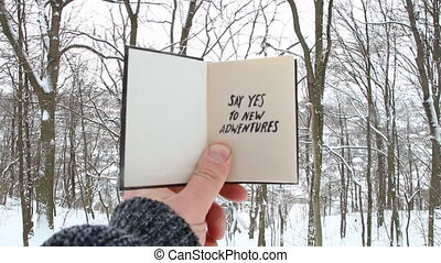 Male holding a book with the inscription Say yes to new adventures on the background of the winter forest