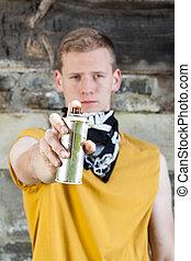 Male hooligan before painting graffiti