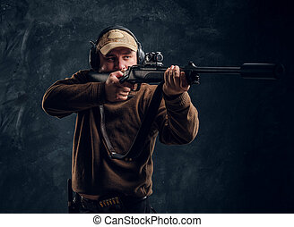 Male hunter in cap and headphones holding a rifle and aiming at his target or prey. Studio photo against a dark wall background