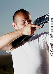 Male hunter in white shirt aiming