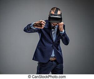 Male in a suit fighting with virtual reality glasses on his...