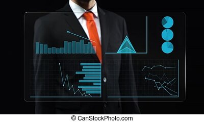 Male in black suit turns-on touchscreen then appears ascending financial chart and diagrams.