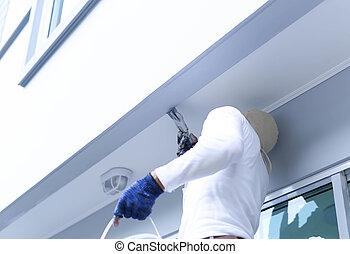 Male in gloves holding pain brush painting building outdoors