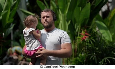 male in headphones with a child in her arms on the street is happening music and dancing. Close-up