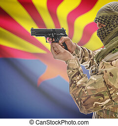 Male in muslim keffiyeh with gun in hand and flag on background - Arizona