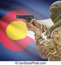 Male in muslim keffiyeh with gun in hand and flag on background - Colorado